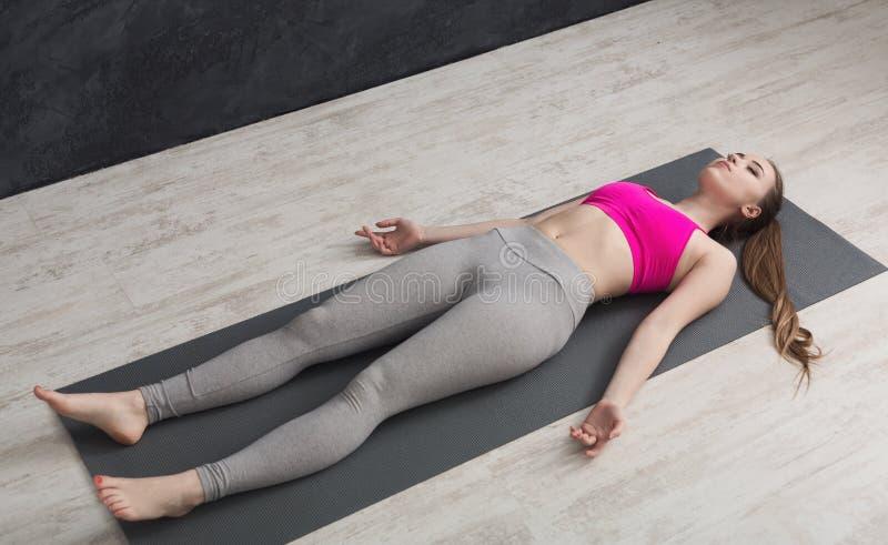 Vrouw die rust na opleidingsyoga hebben in gymnastiek royalty-vrije stock afbeelding