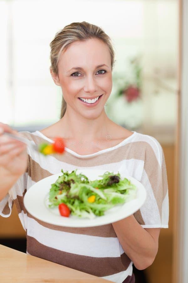 Vrouw die salade aanbieden stock foto
