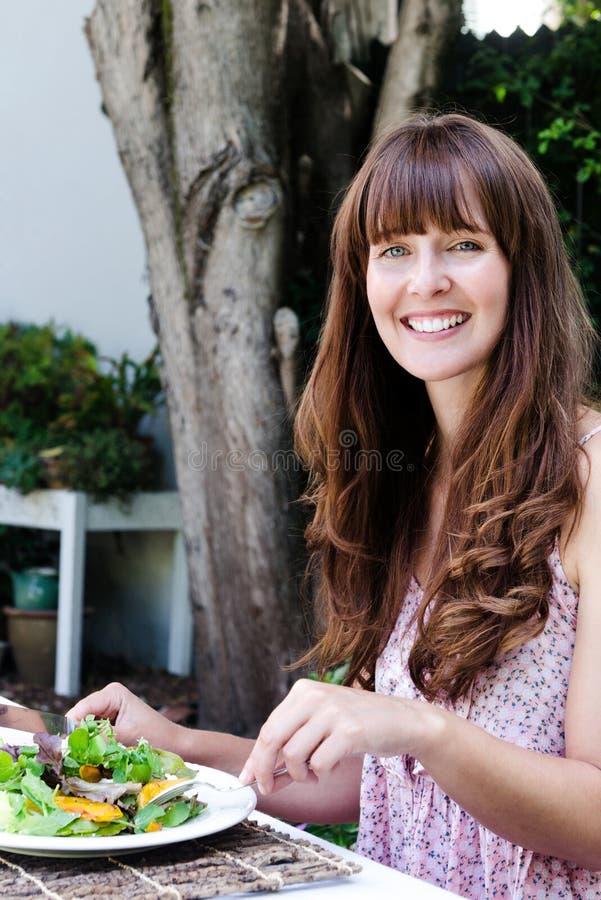 Vrouw die salade, dineren het in de open lucht eten stock foto