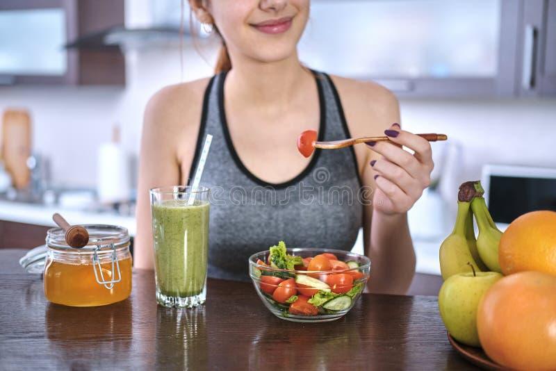 Vrouw die salade op de huiskeuken eten na een training stock foto