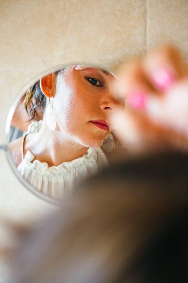 Vrouw die samenstelling in spiegel doen royalty-vrije stock fotografie