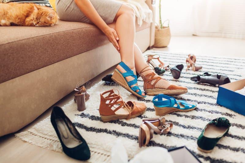 Vrouw die schoenen kiezen en hen thuis proberen op Harde keus van sandals, hielen en vlakten te maken stock foto's