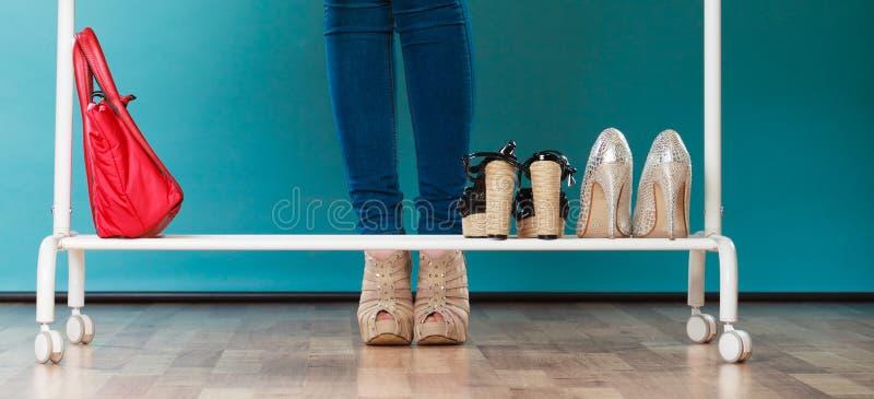 Vrouw die schoenen in wandelgalerij of garderobe kiezen te dragen stock foto's