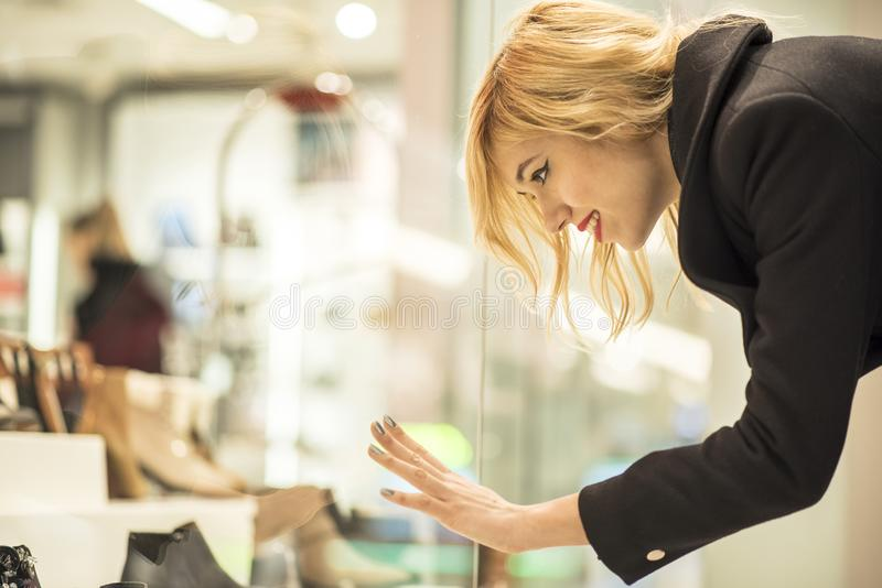 Vrouw die schoenen in winkelvenster zien dat zij werkelijk van heeft gehouden stock fotografie