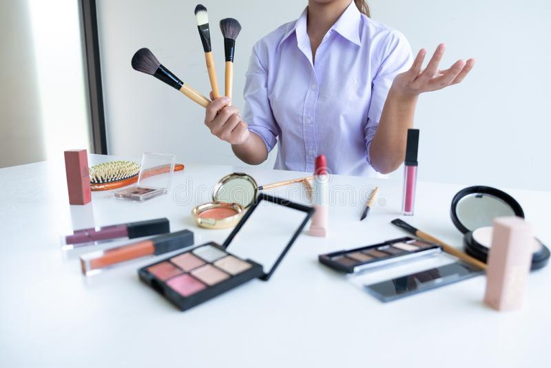 Vrouw die schoonheidscosmetische product en uitzending tonen aan sociaal netwerk door Internet, schoonheid blogger online marketi stock afbeelding