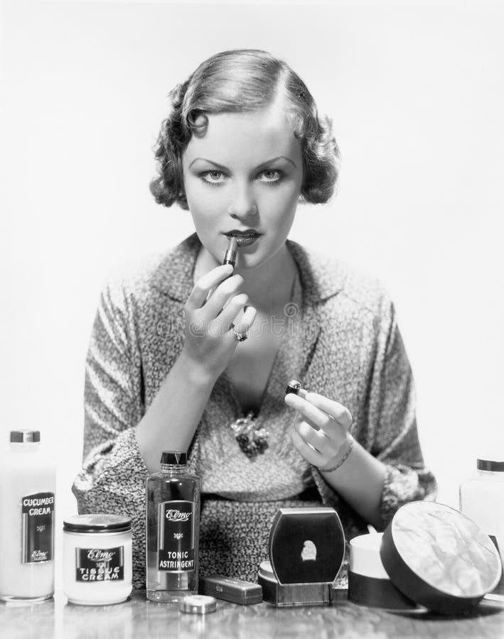 Vrouw die schoonheidsmiddelen toepassen (Alle afgeschilderde personen leven niet langer en geen landgoed bestaat Leveranciersgara stock afbeelding