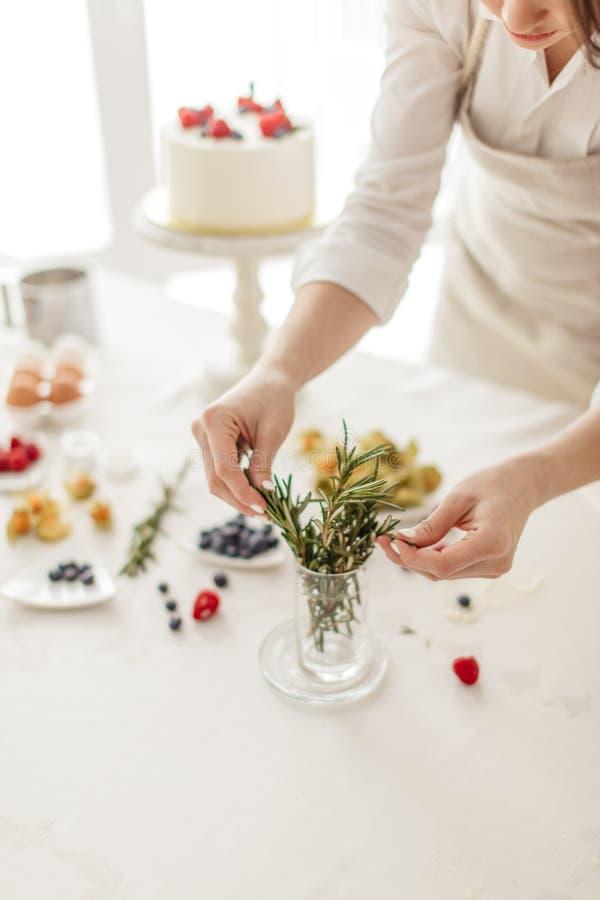 Vrouw die in schort bladeren voor decoratie van cake kiezen stock afbeeldingen