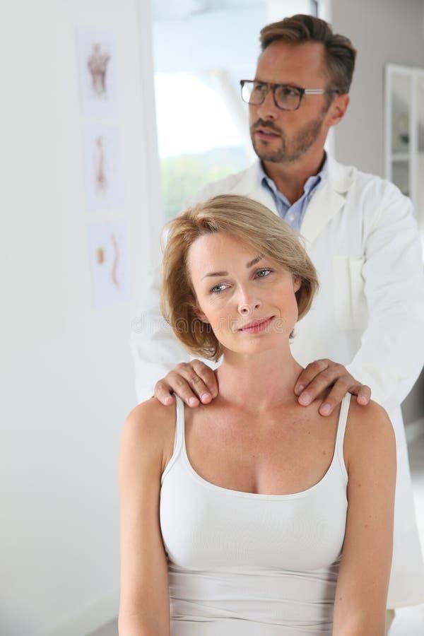 Vrouw die schoudermassage door chiropracticus hebben stock fotografie
