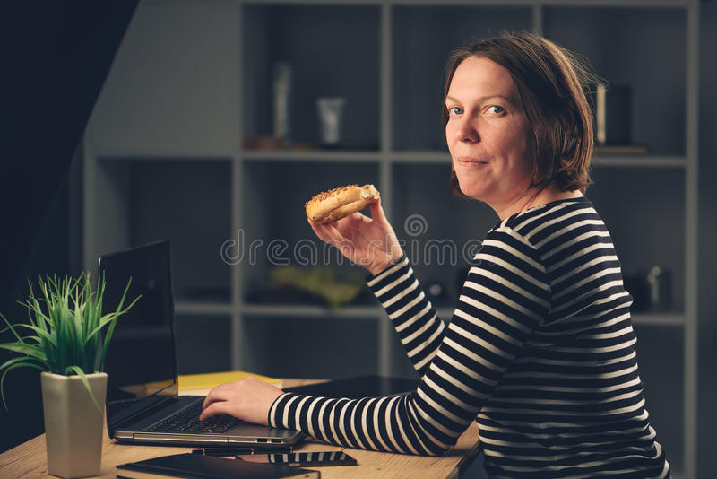 Vrouw die sesamongezuurd broodje in bureau eten stock foto