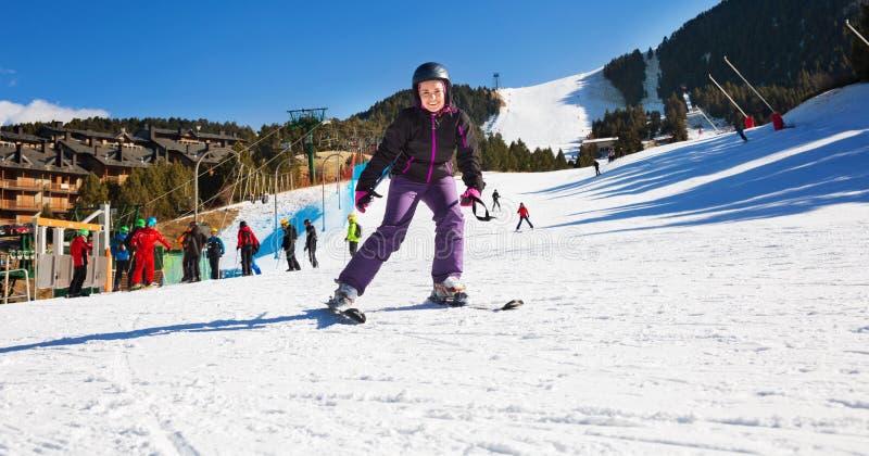 Vrouw die skimateriaal dragen en in sneeuwende bergen ski?en stock fotografie