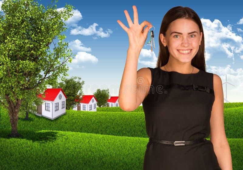 Vrouw die sleutel en huizen met landschap tonen stock afbeelding
