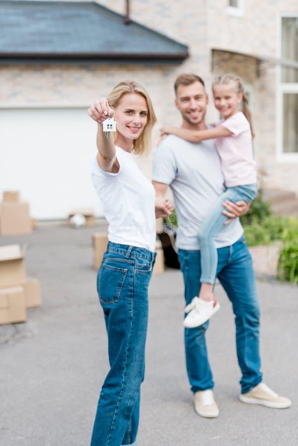 vrouw die sleutel met trinket en haar echtgenoot tonen die zich erachter en dochter voor hun nieuw bevinden houden royalty-vrije stock foto's