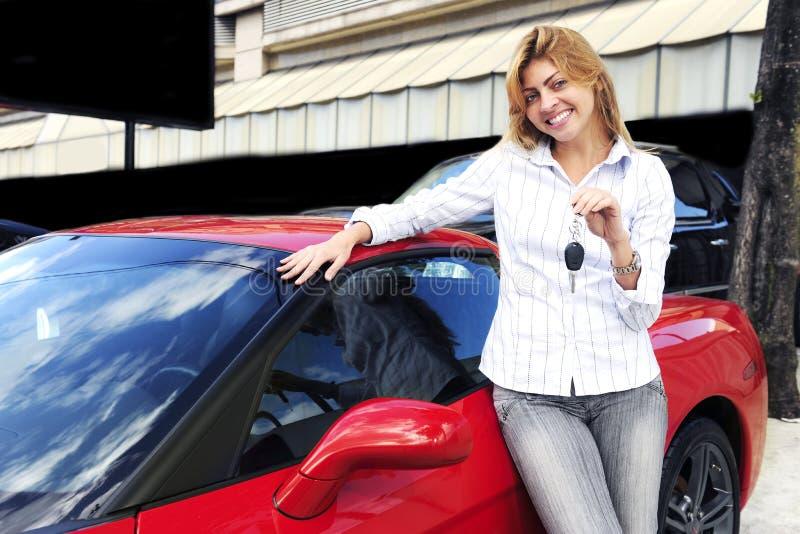 Vrouw die sleutel van nieuwe sportwagen toont stock fotografie