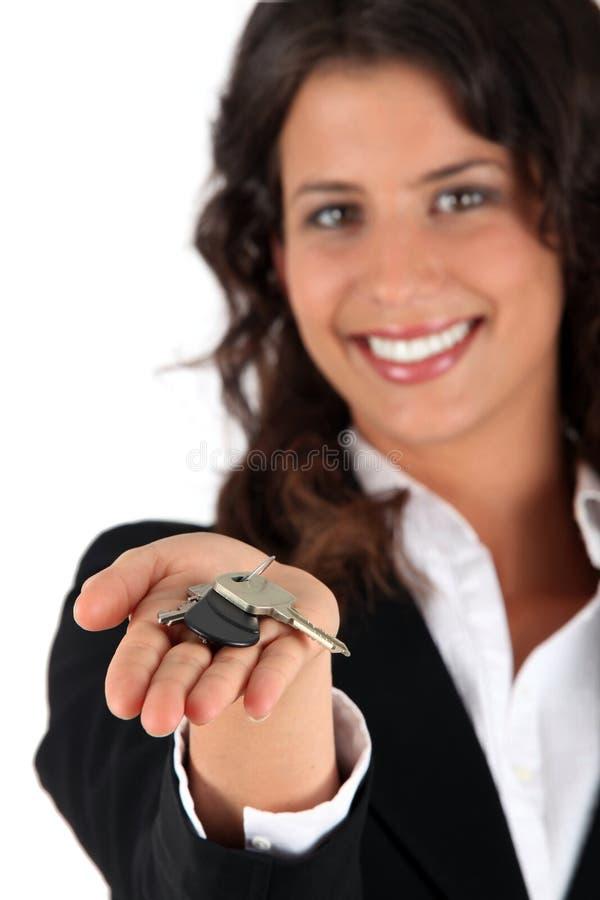 Vrouw die sleutels geeft stock afbeeldingen