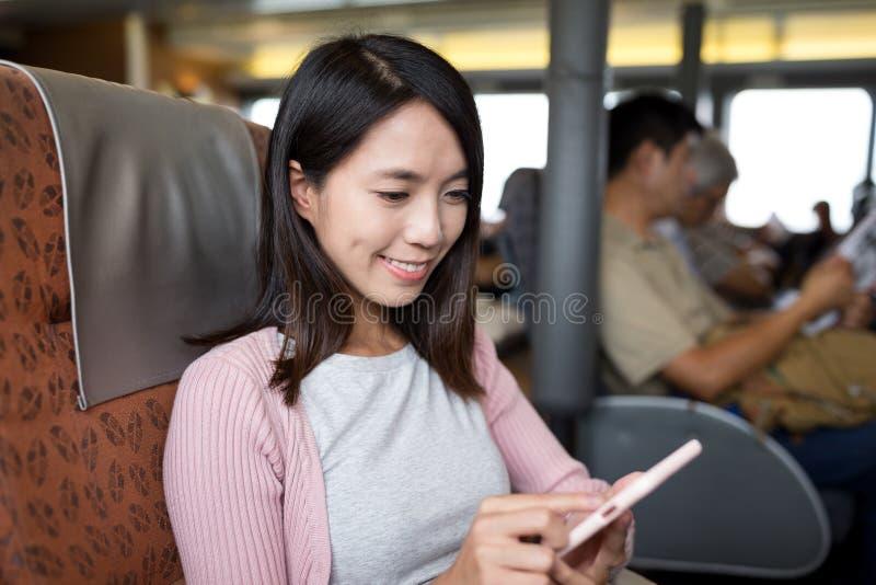 Vrouw die slimme telefoon binnen schip met behulp van royalty-vrije stock afbeelding