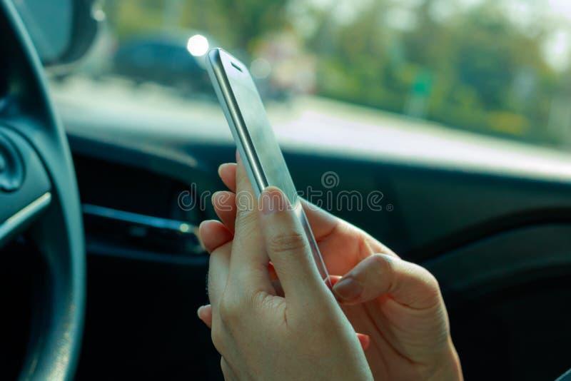Vrouw die slimme telefoon op de auto met behulp van stock foto