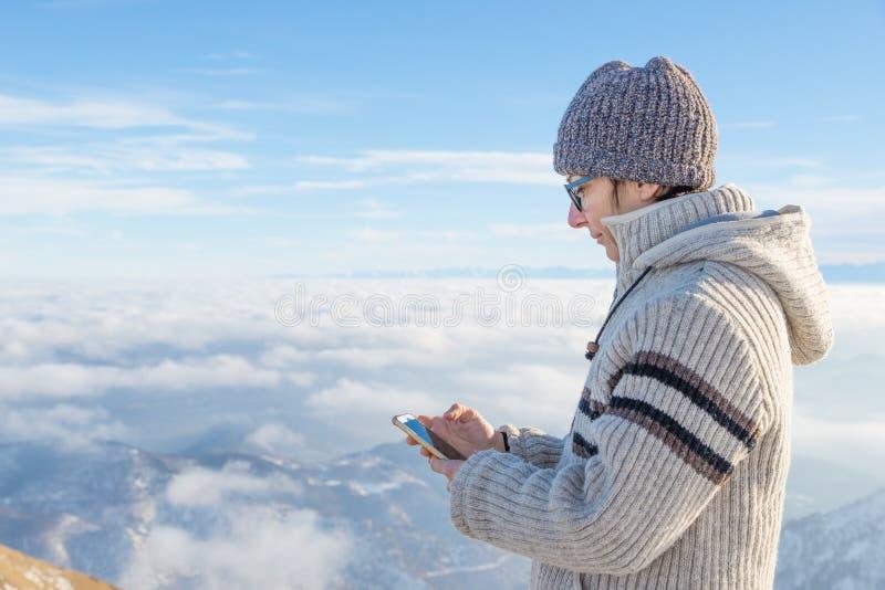 Vrouw die slimme telefoon op de bergen met behulp van Panorama van snowcapped Alpen in koude wintertijd Concept het delen van het royalty-vrije stock afbeeldingen