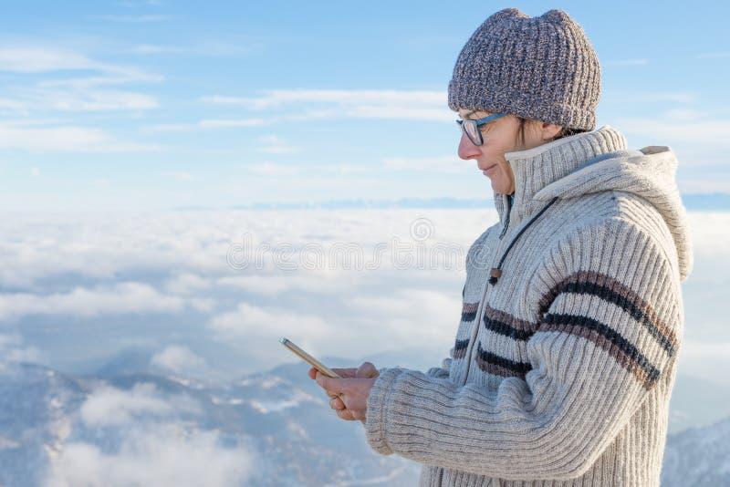 Vrouw die slimme telefoon op de bergen met behulp van Panorama van snowcapped Alpen in koude wintertijd Concept het delen van het stock foto's