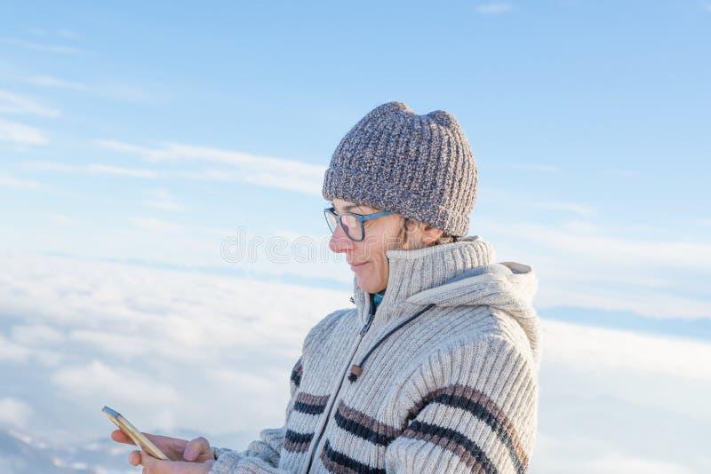 Vrouw die slimme telefoon op de bergen met behulp van Panorama van snowcapped Alpen in koude wintertijd Concept het delen van het stock afbeeldingen