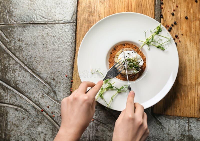 Vrouw die smakelijk haringentandsteen met gestroopt ei op lijst eten royalty-vrije stock foto's
