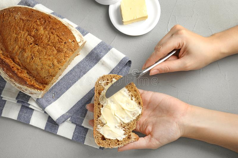 Vrouw die smakelijke boter op brood over grijze lijst uitspreidt stock foto