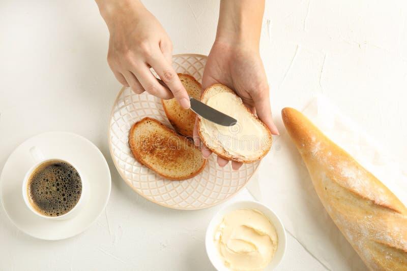 Vrouw die smakelijke boter op brood over plaat uitspreiden bij witte lijst, royalty-vrije stock afbeelding