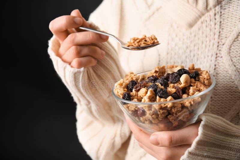 Vrouw die smakelijke granola met droge vruchten op donkere achtergrond eten stock fotografie