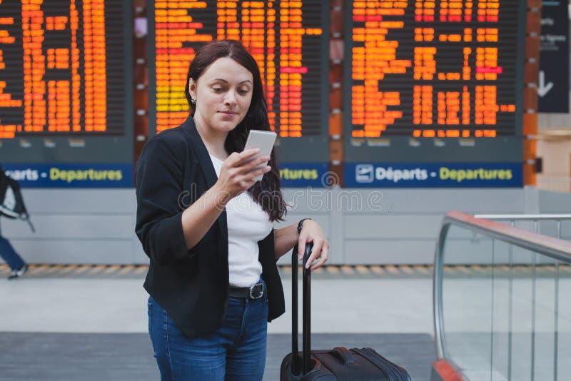Vrouw die smartphone in internationale luchthaven gebruiken royalty-vrije stock fotografie