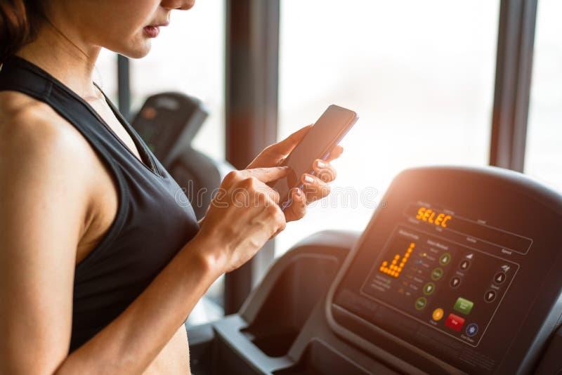 Vrouw die smartphone met behulp van wanneer training of sterkte opleiding bij geschiktheidsgymnastiek op tredmolen Ontspan en tec stock foto's