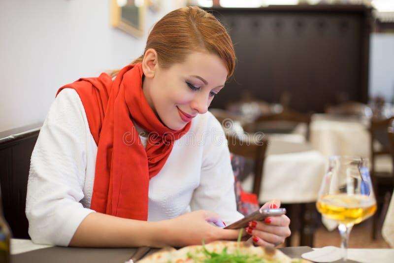 Vrouw die smartphone, mobiele telefoon in het Italiaans gebruiken restaurant royalty-vrije stock foto's