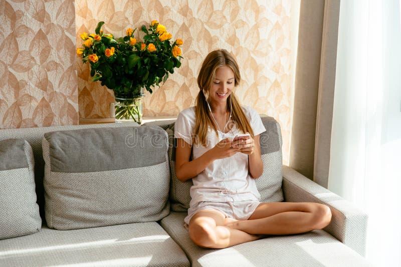Vrouw die smartphone op bank thuis gebruiken stock afbeelding