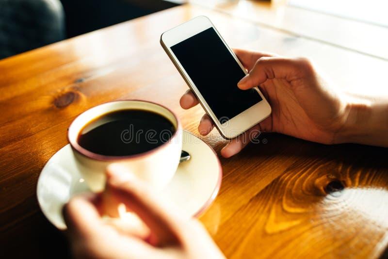 Vrouw die smartphone op houten lijst in koffie gebruiken royalty-vrije stock afbeeldingen