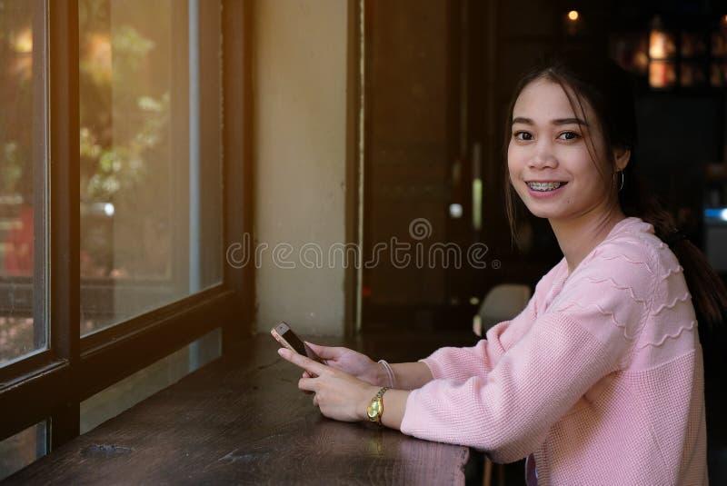 Vrouw die smartphone op houten lijst met behulp van stock foto
