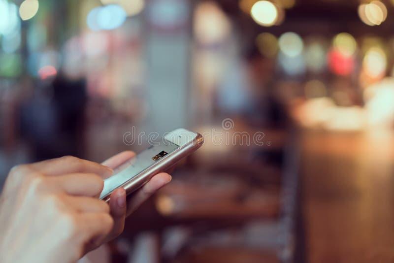Vrouw die smartphone op koffie gebruiken, tijdens vrije tijd Het concept het gebruiken van de telefoon is essentieel in het dagel stock fotografie