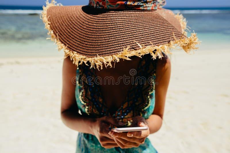 Vrouw die smartphone op strand gebruiken royalty-vrije stock afbeelding