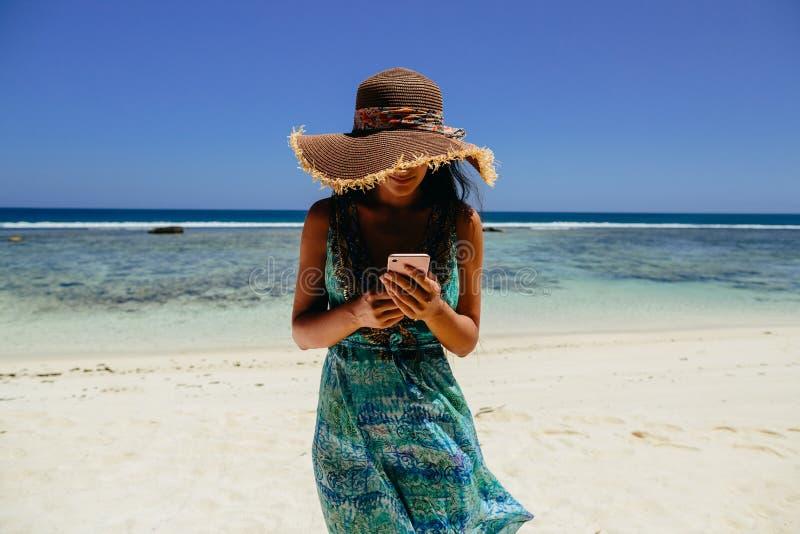 Vrouw die smartphone op strand gebruiken royalty-vrije stock fotografie