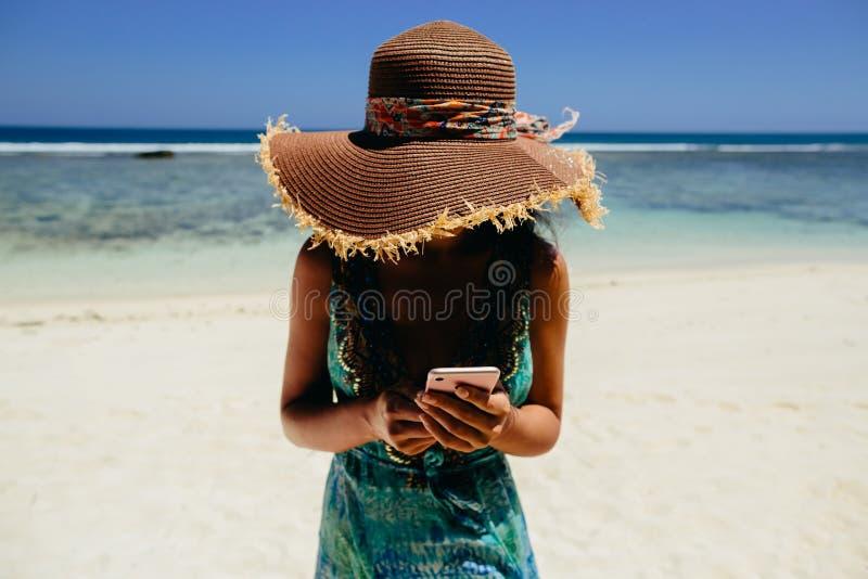 Vrouw die smartphone op strand gebruiken royalty-vrije stock foto