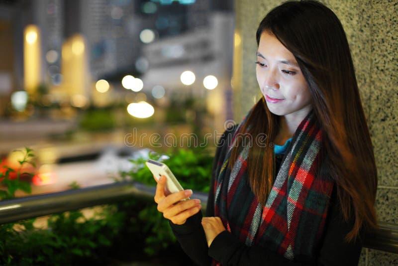 Vrouw die smartphone in stad gebruiken royalty-vrije stock afbeelding