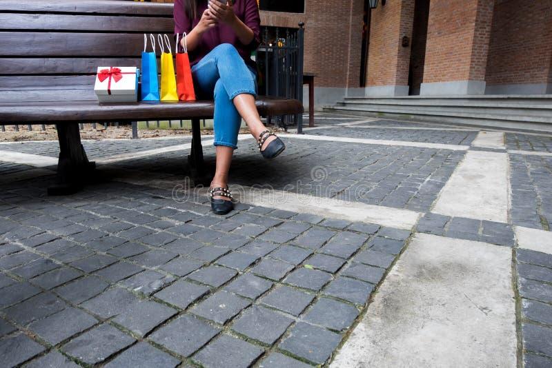 Vrouw die smartphone voor het winkelen online in winkelcomplex gebruiken stock foto