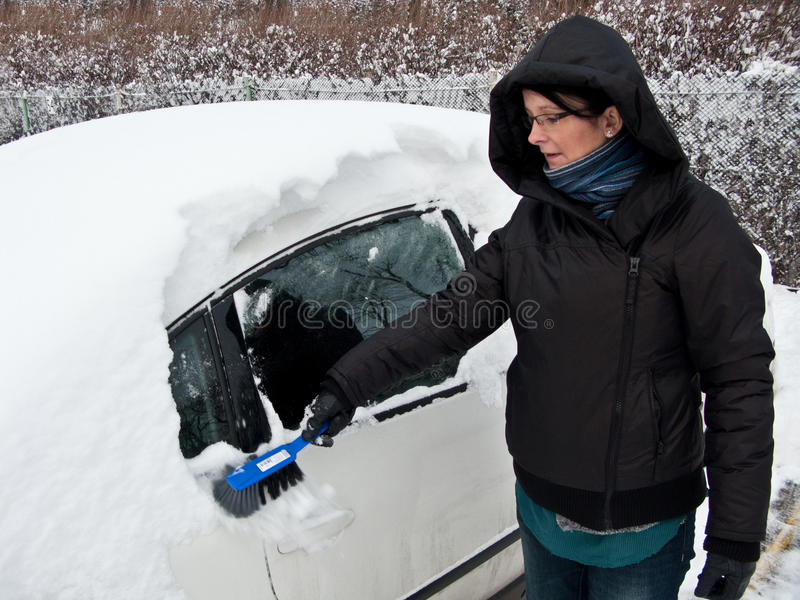 Vrouw die sneeuw verwijdert uit auto stock foto's