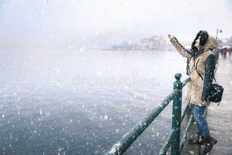 Vrouw die sneeuwvlokken op een sneeuwdag bereiken royalty-vrije stock fotografie