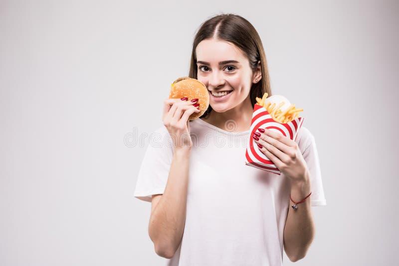 Vrouw die snel voedselhamburger met Frans eten die op grijs portret wordt gebraden als achtergrond Het concept van de gezondheid stock foto