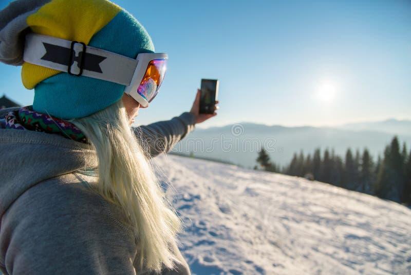Vrouw die snowboarder na snowboarding ontspannen, die foto's van de winteraard nemen in de bergen die smartphone met behulp van stock afbeelding