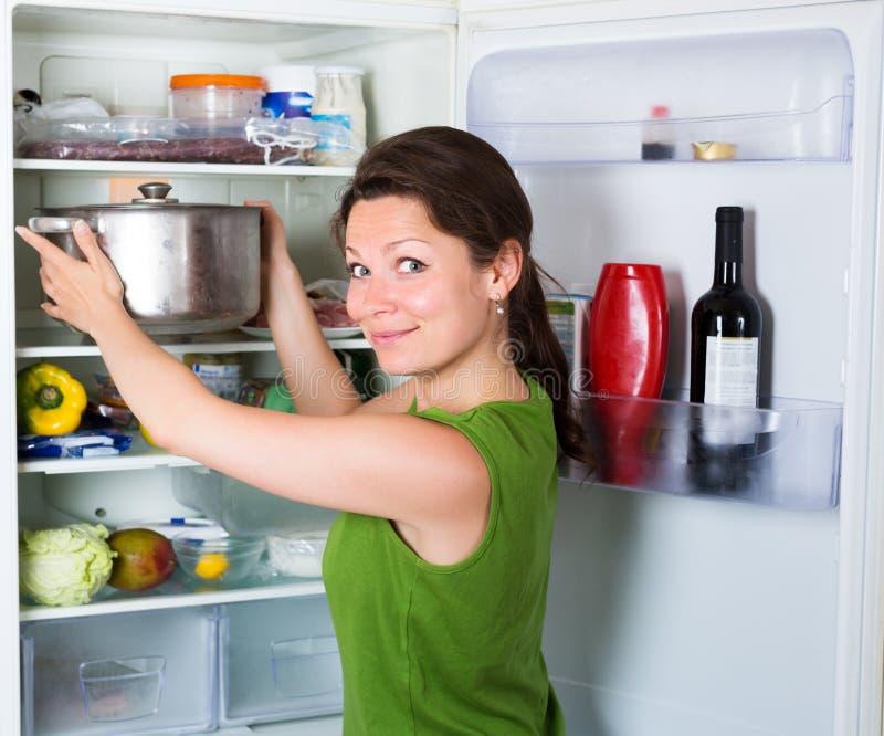 Vrouw die soep van pan eten stock fotografie