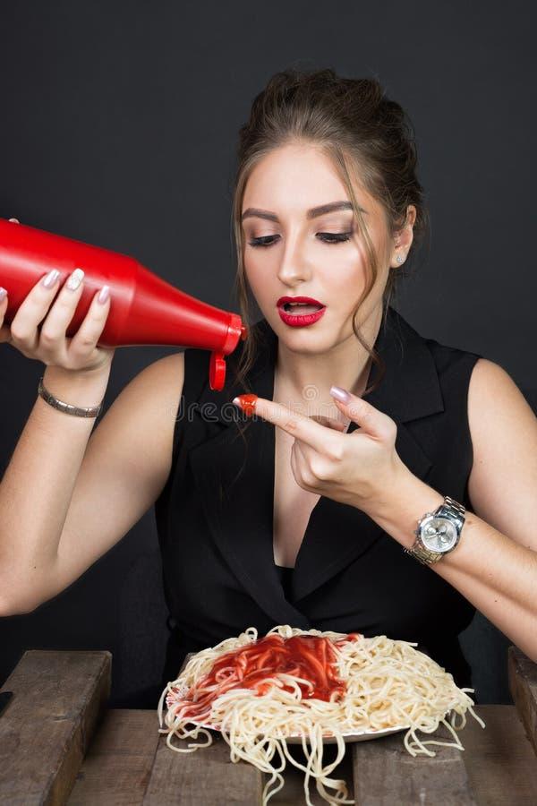 Vrouw die spaghetti eten bij houten lijst stock afbeeldingen