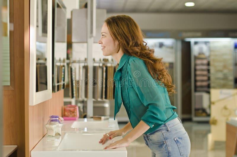 Vrouw die spiegel bad en loodgieterswerkopslag bekijken royalty-vrije stock afbeeldingen