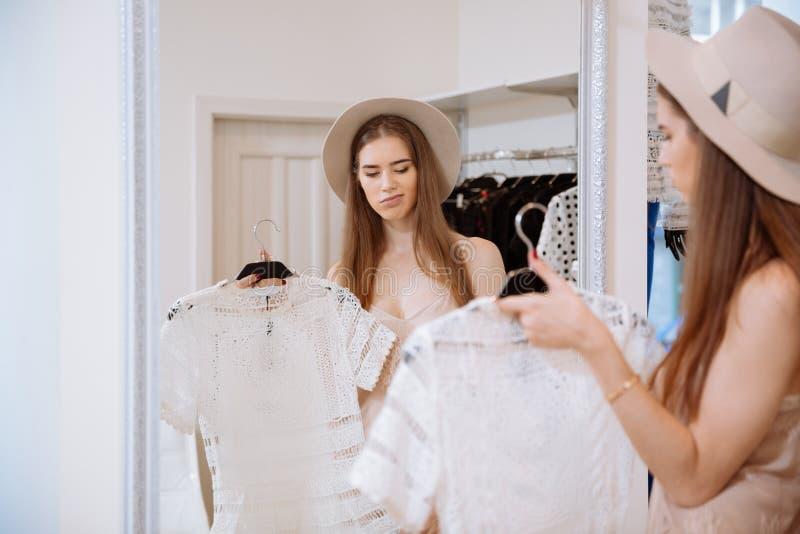 Vrouw die spiegel bekijken en kleding in kledingswinkel kiezen royalty-vrije stock afbeeldingen
