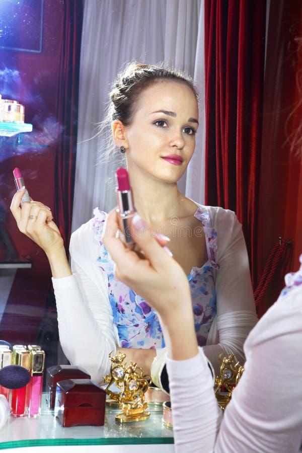 Vrouw die spiegel bekijkt stock afbeeldingen