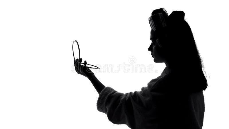 Vrouw die in spiegel kijken, die haarrollen voor kapsel, voorbereiding voor datum met behulp van stock foto's