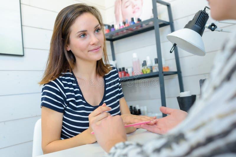 Vrouw die spijkermanicure doen stock fotografie